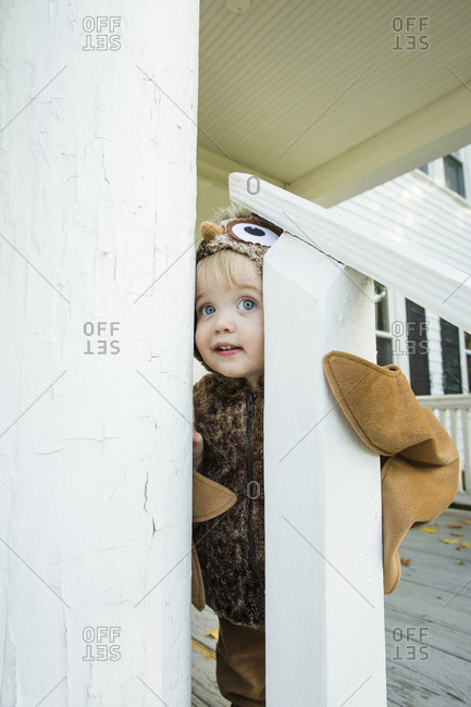 Curious dressed up toddler boy looks through railing during Halloween