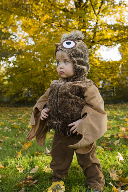 Toddler boy stands looking to the side while dressed up in costume