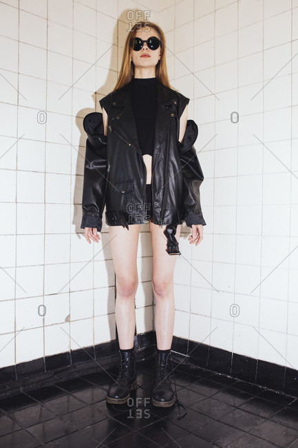 A woman in a leather jacket and glasses stands in a tiled room.