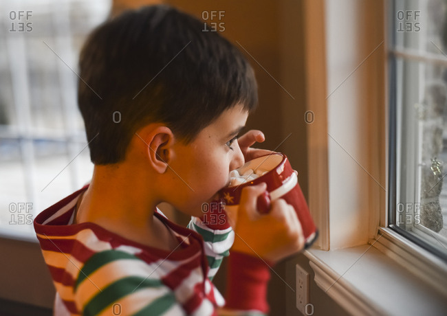 Young boy in Christmas pjs drinking hot cocoa looking out the window.