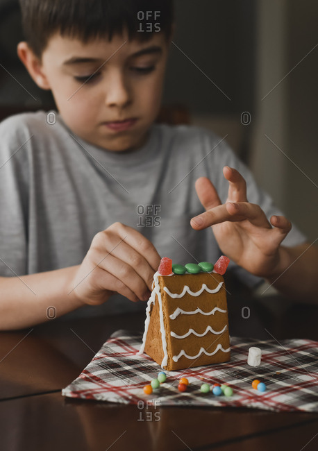 Close up of young boy putting candies on a gingerbread house.