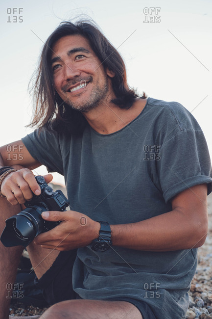 Person smiling at the camera on the beach while using camera
