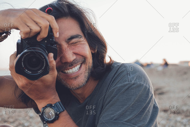 Person smiling at the camera on the beach while using his camera