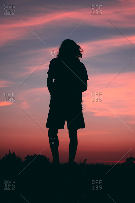 Person at the top of hill watching the sunset