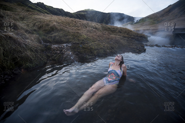 Pretty woman lying on back in thermal water river.