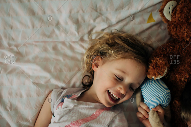 young blonde girl smiling and laughing in her bedroom with soft toys