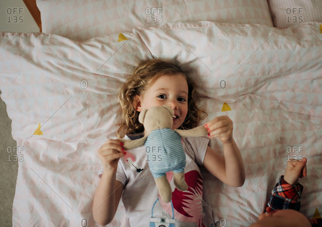 young girl laying on her bed with soft toys smiling in her bedroom
