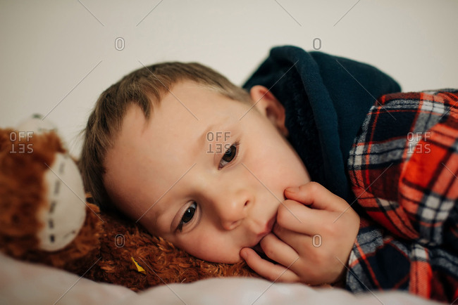 young blonde boy aged 6 laying down tired on his bed with teddy bear