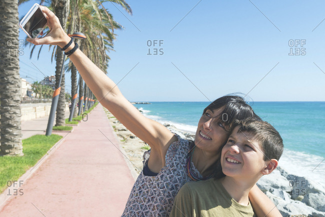 Mom and son standing next to beach while taking a selfie
