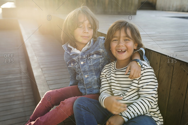 Smiling portrait of two siblings  on a rooftop in Barcelona