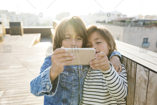 Two siblings taking a selfie with a smart phone on a rooftop