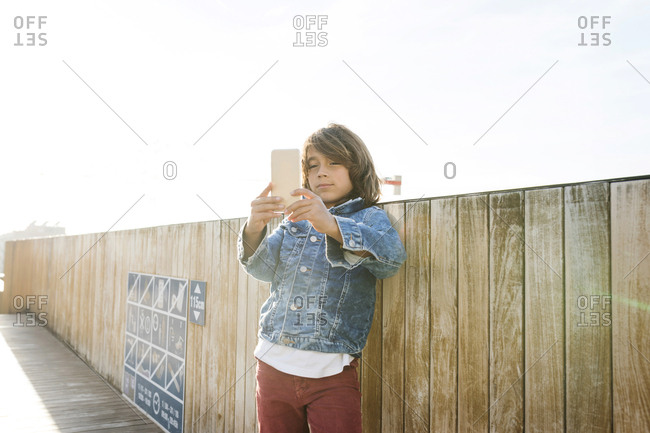 Young boy taking a selfie with a smart phone on a rooftop in barcelona