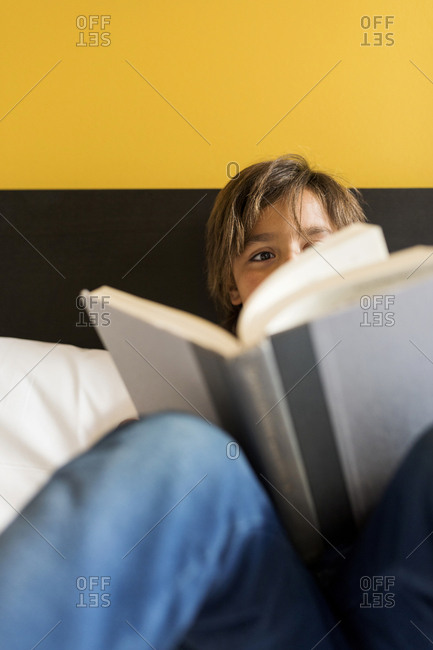 young boy in a yellow bedroom reading a book on bed