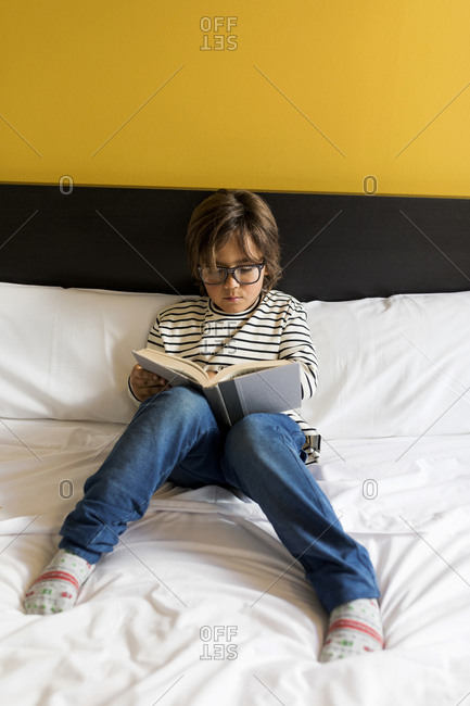Adorable kid with modern glasses  reading a book on bed