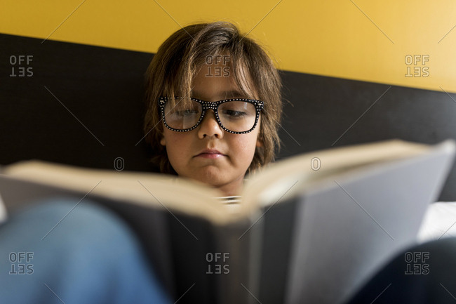 Thoughtful kid with modern glasses  reading a book on bed