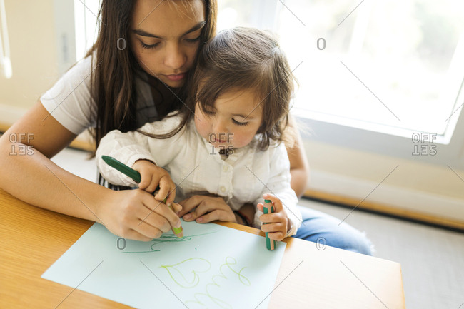 Nanny helping a toddler with a drawing with colored pencils at home