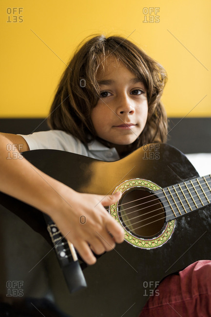 Little boy practicing classic guitar on his bed against yellow wall