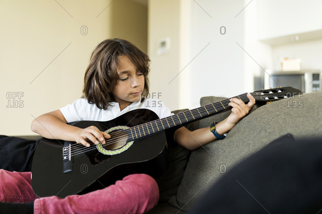young boy  playing guitar sitting on the sofa at home