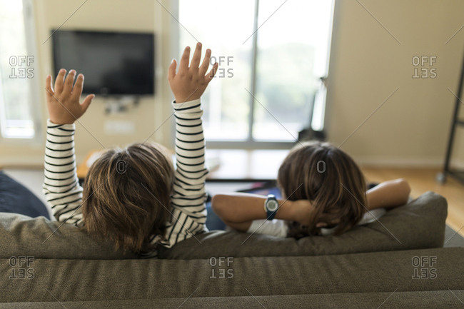 two kids from back sitting on the couch playing with a tablet