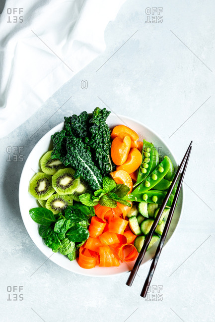 Assorted vegetable bowl with chopsticks and a napkin