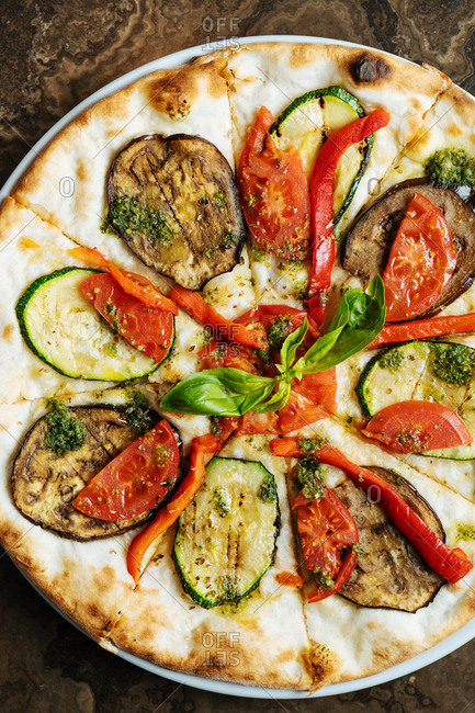 Close up of whole pizza topped with veggies