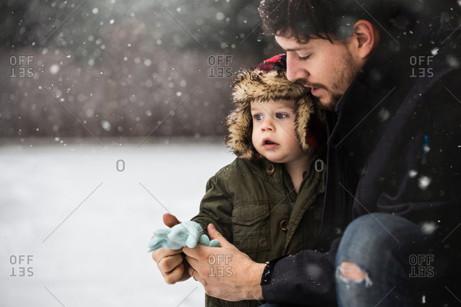 Man putting gloves on baby boy in the snow