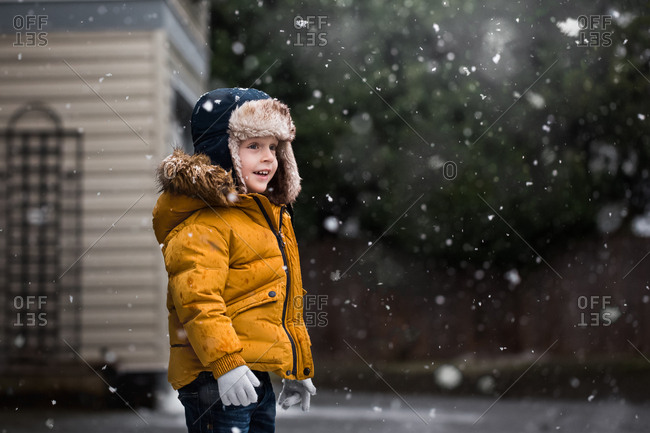 Boy wearing yellow jacket and bomber hat in the snow