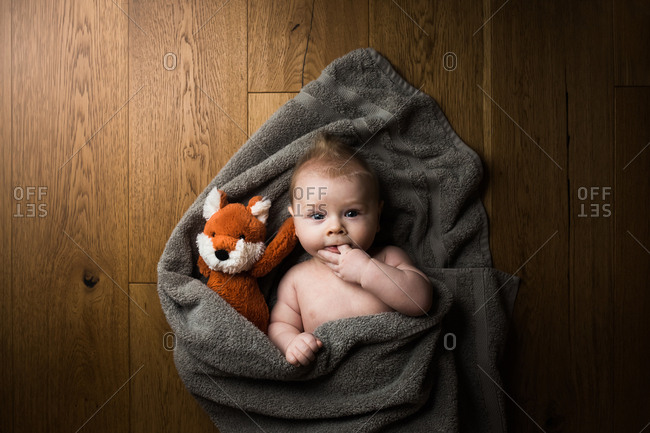 Baby boy with stuffed fox wrapped in towel after bath
