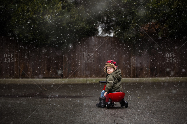 Toddler boy playing on ride on toy in the snowfall
