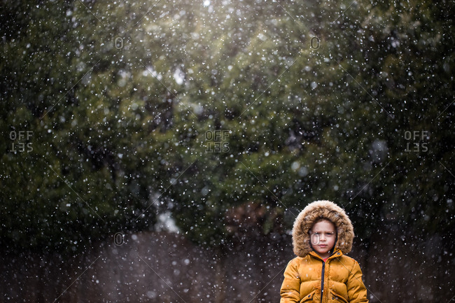 Toddler boy pouting while outside on snowy day