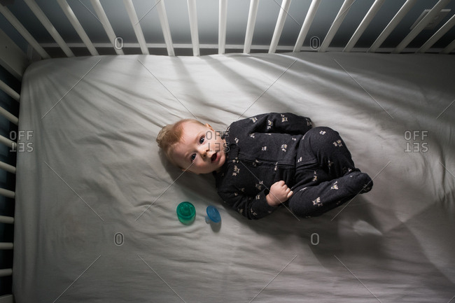 Overhead view of baby in crib with pacifiers