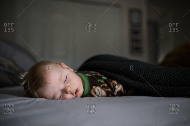 Baby boy sleeping on bed