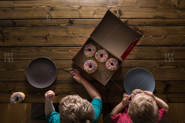Brothers eating sprinkle donuts from above