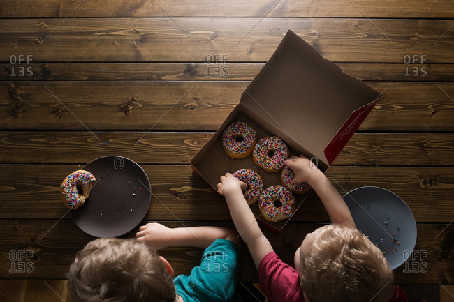 Two boys eating sprinkle donuts from above