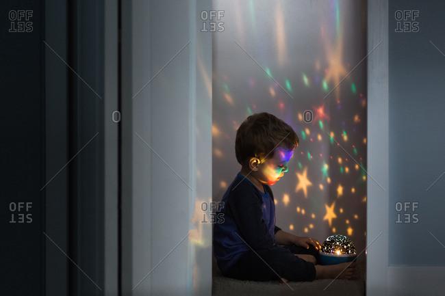 Toddler boy watching star light projector