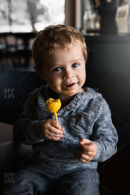 Toddler boy eating a yellow cake pop