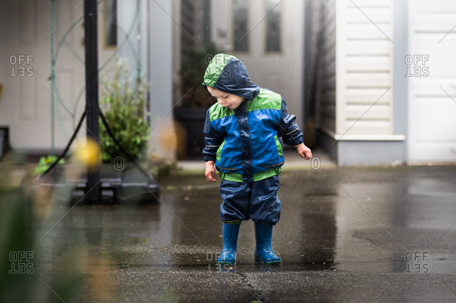 Boy dressed in rain coat and boots splashing in puddles