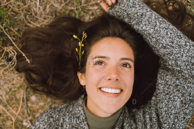 Portrait of happy and positive young woman with a flower