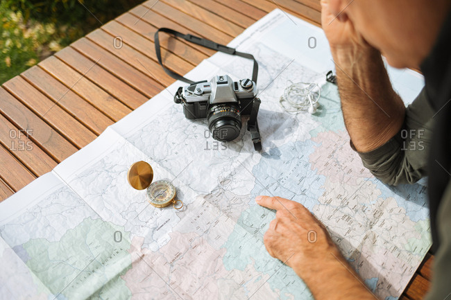 Hands of a man pointing at a map, on a wooden table