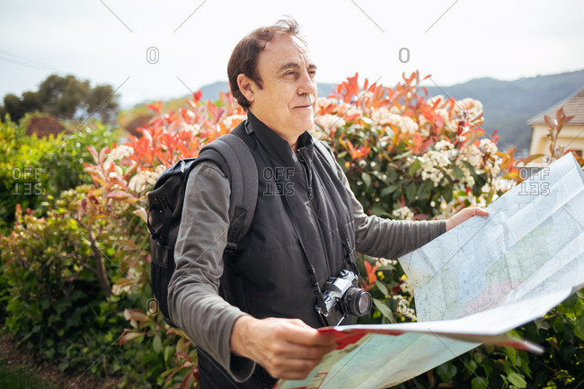 50-60 years old man holding a map with confident look