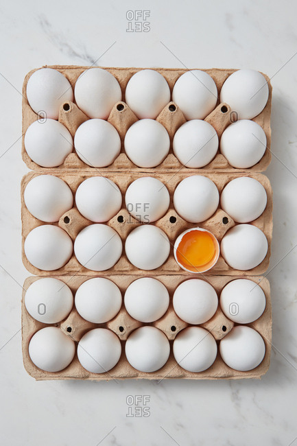 Organic raw chicken eggs and one broken egg in a carton box on a gray marble background. Easter concept. Flat lay