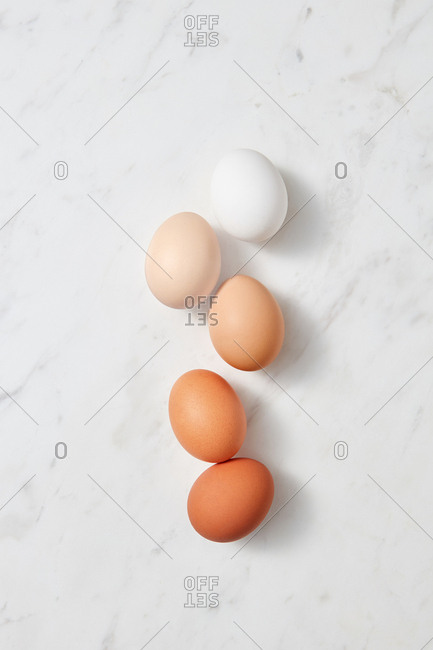 Collection of different chicken eggs on a gray marble background with copy space. Easter layout. Flat lay