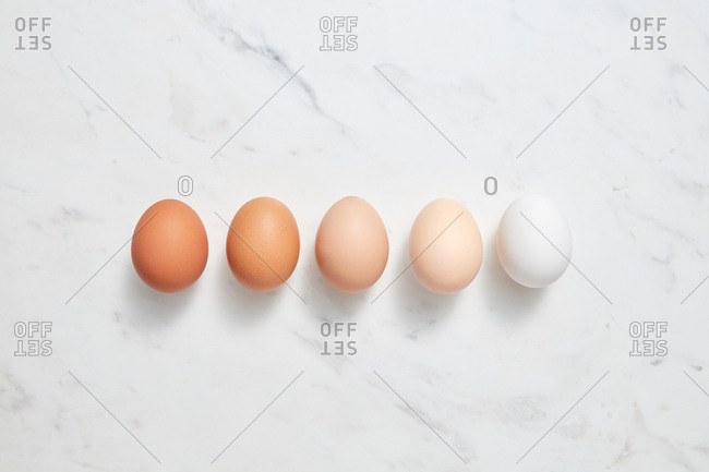Set of different chicken eggs on a gray marble background with space for text. Easter layout. Flat lay