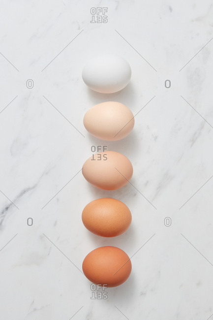 Row of colorful organic eggs on a gray marbled background with copy space. Easter concept. Flat lay