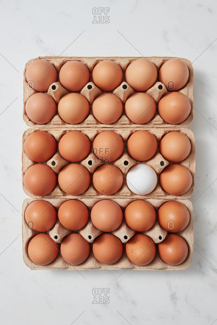 Brown and white chicken eggs in a carton box on a marble table with copy space as layout for your ideas. Easter concept. Flat lay