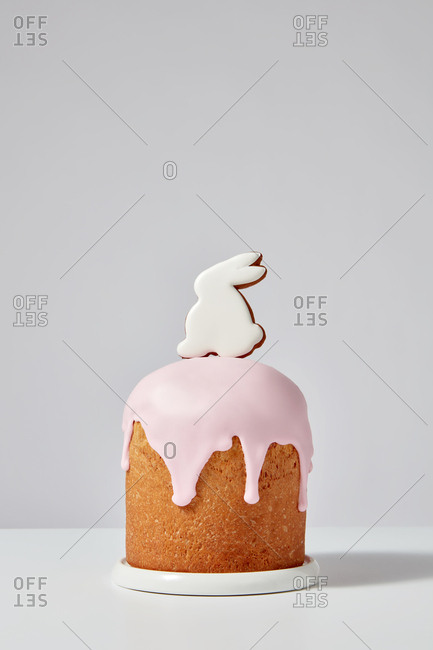 Homemade Easter cake with pink icing and bunny cookies presented in a white plate on a gray background with space for text