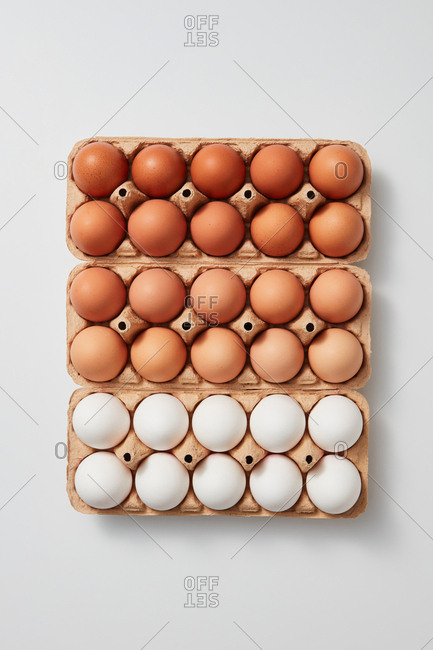 White and brown organic eggs in cardboard boxes presented on a gray background with space for text. Healthy product. Flat lay