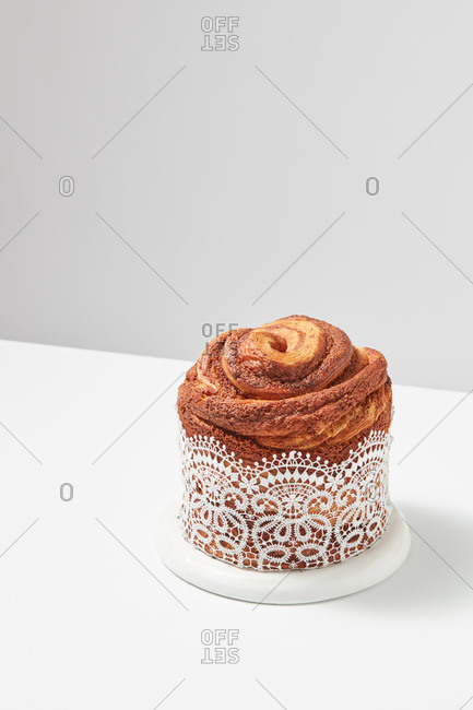 Freshly baked Easter cake decorated with lace on a white table around a gray background with copy space. Traditional festive dessert