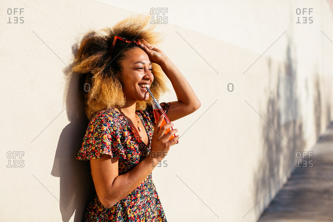 Portrait of a woman with afro hairstyle drinking healthy juice on summer.