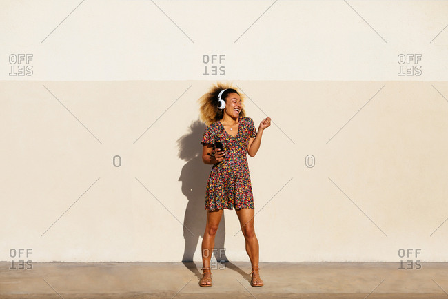 Woman with afro hairstyle singing listening music on phone.